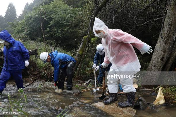 Local residents and members of the fire brigade search for a woman who went missing during a landslide one year ago when powerful Typhoon Hagibis hit...