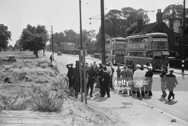 Local residents and workers crowd around the entrance to an air raid shelter to watch advancing German Luftwaffe bombers in the sky over Croydon in...