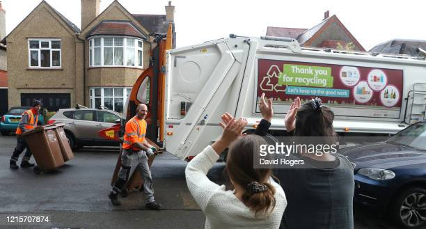 Local residents applaud as waste bins are collected by refuse collectors on March 30, 2020 in Northampton, England. The Coronavirus pandemic has...