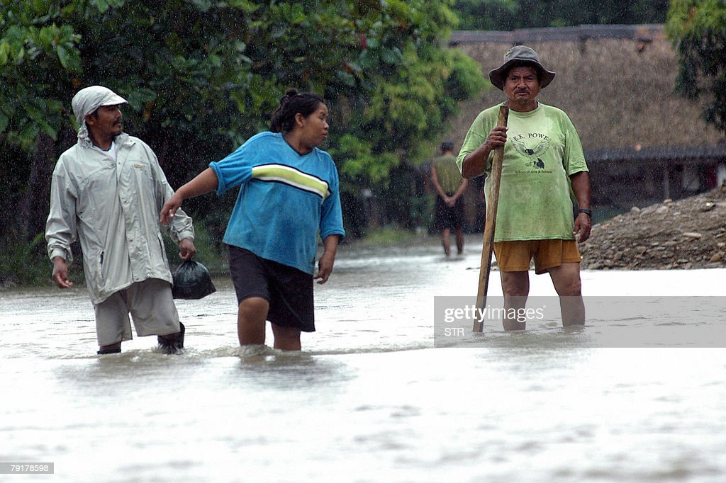 Local residents attempt to cross a flooded street in Villarroel, some 270km east of Cochabamba, center Bolivia, after the overflowing of the Ichilo and Sajta rivers, 23 January, 2008. The Bolivian government decreed on Tuesday a national emergency to counteract damages caused by heavy rains and floods battering the country since last November. According to last official sources, 27 people died so far, four are still missing and about 21,500 families have been seriously damaged.