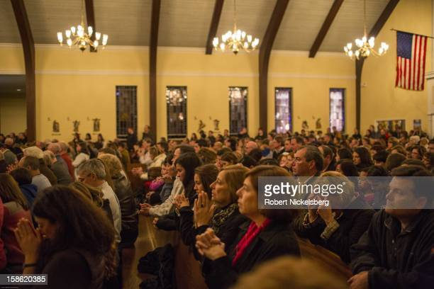 Local residents attend a memorial service at the Saint Rose Roman Catholic Church December 14 2012 in Newtown Connecticut for the 28 children and...