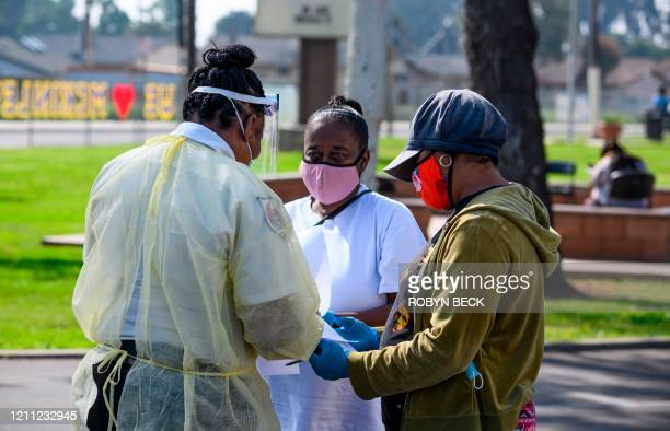 Local residents Burnetta Kinsey and Zina Parker fill out paperwork at a mobile COVID19 testing station in a public school parking area in Compton...