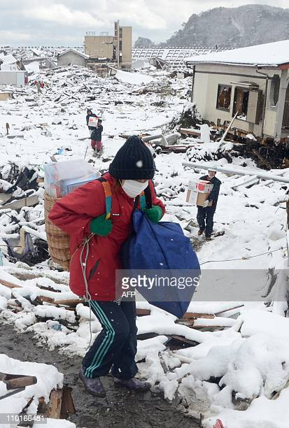 Local residents carry belongings salvaged from their home damaged by the March 11 tsunami in Miyako in Iwate prefecture on March 16 2011 Japan's...