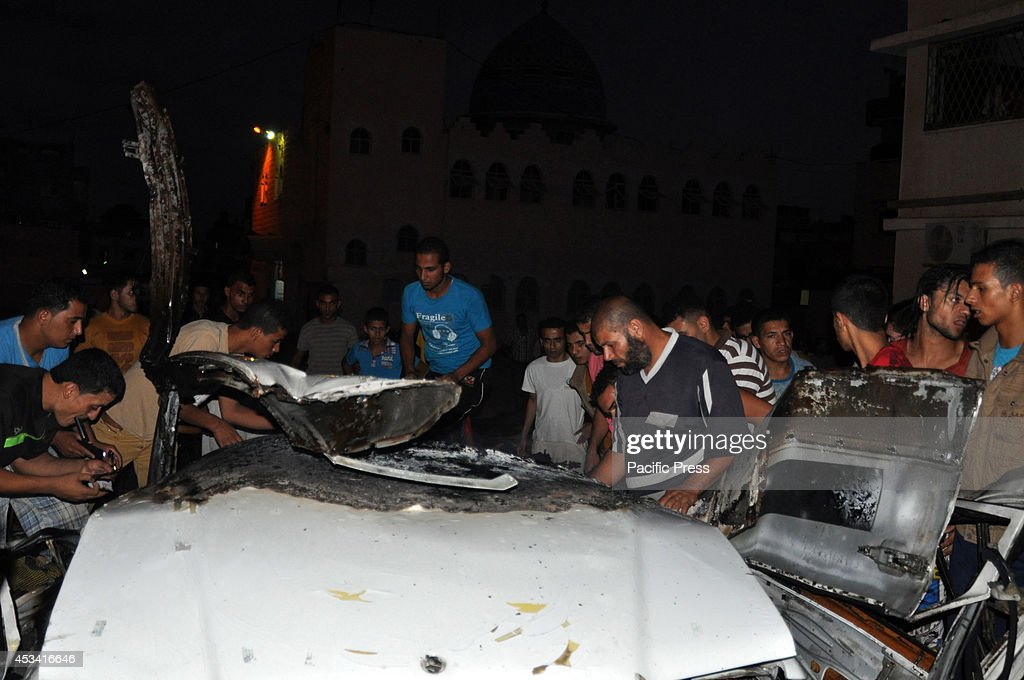 Local residents checking the wreckage of a car, which was... : ニュース写真