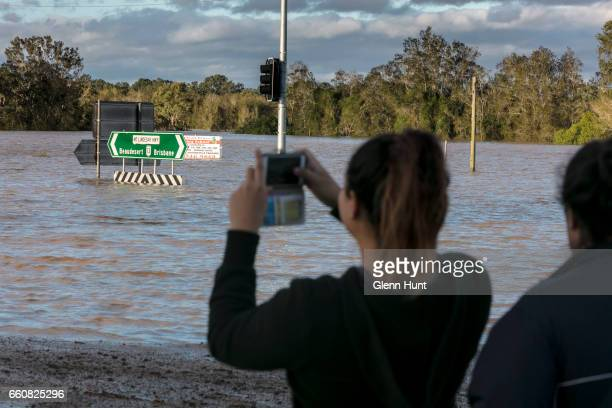 Local residents Christie and Haleigh McIntyre watches on as the Logan River near Beaudesert floods surrounding areas on March 31 2017 in Brisbane...