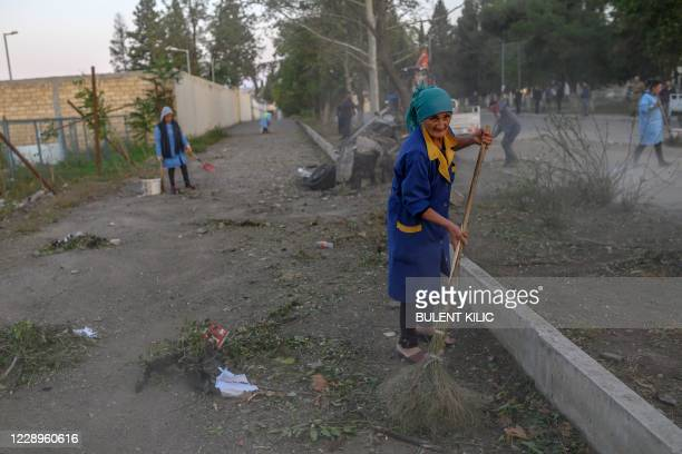 Local residents clean a street after it was hit by a missile in Gandja, Azerbaijan, on October 8 near the disputed Nagorno-Karabakh province's...