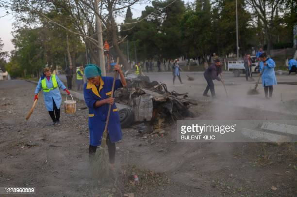 Local residents clean a street in Gandja, Azerbaijan, on October 8 near the disputed Nagorno-Karabakh province's capital Stepanakert, that was hit by...