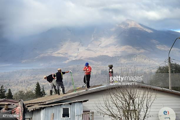 Local residents clean the roof of their home from ashes of the Calbuco volcano at La Ensenada, southern Chile, on April 25, 2015. Authorities ordered...