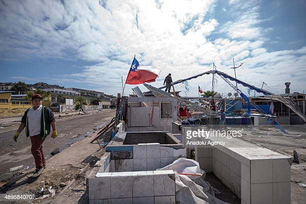 Local residents clean their home of the debris left by the tsunami that ensued an 83 quake that left 12 people dead in Coquimbo 450 km north of...