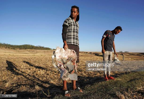 Local residents collect debris at the scene where Ethiopian Airlines Flight 302 crashed in a wheat field just outside the town of Bishoftu 62...