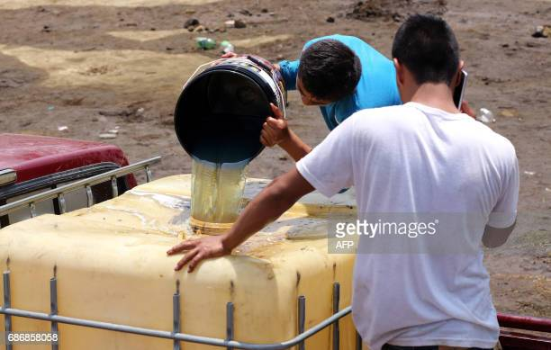 Local residents collect diesel fuel from a leaking pipe with the permission of workers from the Mexican oil company Pemex in the community of San...