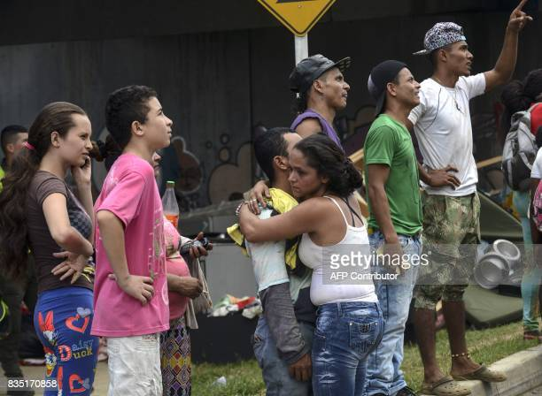 Local residents comfort each other during a raging fire in the Moravia neighborhood in Medellin on August 18 2017 The Moravia sector is known for...