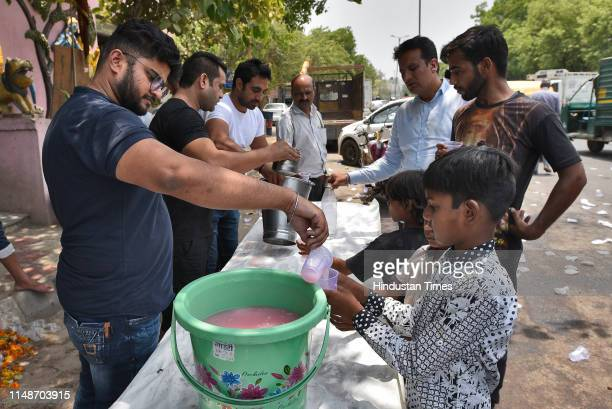Local residents distribute flavoured water as a goodwill gesture to passersby on a summer day, at Chattarpur, on June 9, 2019 in New Delhi, India....