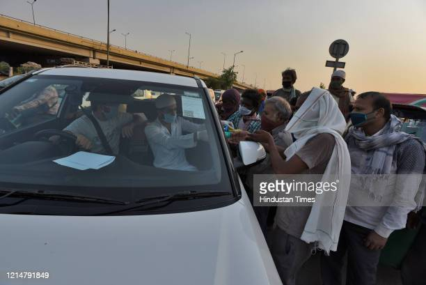 Local residents distribute food and water to migrants stranded at the Ghazipur Delhi Uttar Pradesh border on May 22 2020 in New Delhi India