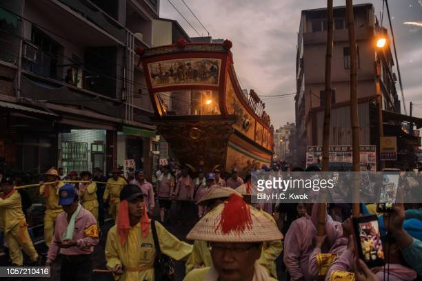 Local residents drag the 'Wang Yeh's Boat' a 13meter finely crafted ancient warship made of paper and wood for burning during the Pingtung Wang Yeh...