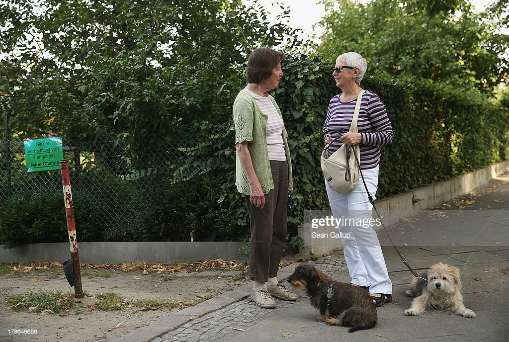 Local residents Edeltrud Strassmeir (L) with her dog Julchen and Christiane Richter with her dog Yosi chat next to an entrance to the Oeynhausen Small Garden Association garden colony where they enjoy walking with their dogs on August 29, 2013 in Berlin, Germany. At the Oeynhausen colony about 300 of its 438 gardens are currently threatened by real estate development, as are about another 24 colonies across the city. Berlin has about 900 garden colonies that are owned by the city and that provide urban dwellers who don't have land of their own the opportunity to maintain a garden and escape the stress of urban life. Berlin is currently undergoing a housing squeeze and city authorities are beginning to sell some of the colonies to developers, which has caused outrage in a city where the colonies of small gardens are a deep-seated tradition going back over a century.
