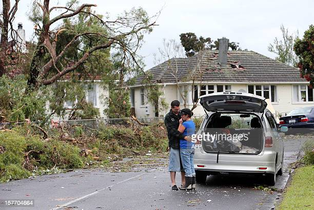 Local residents embrace on a street in front of a damaged house and debris in Hobsonville Auckland on December 6 2012 after packed wind gusts of up...