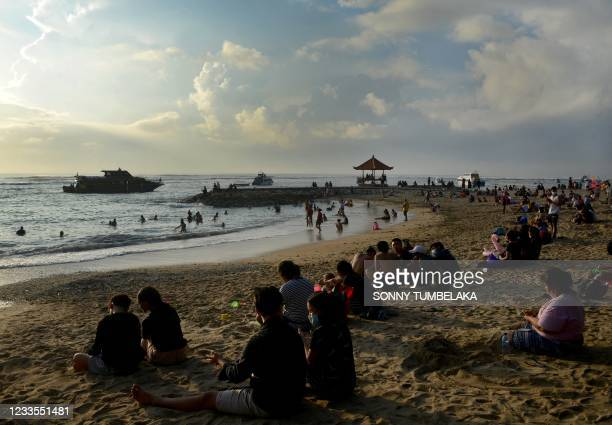 Local residents enjoy an early morning swim along Sanur beach as boats arrive to pick up passengers to cross to the nearby tourist island of Nusa...