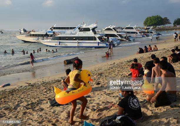 Local residents enjoy an early morning swim along Sanur beach as boats line up to prepare to load passengers to cross to the nearby tourist island of...