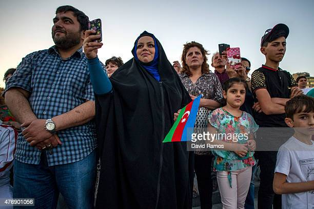 Local residents enjoy the atmosphere as they watch the Opening Ceremony for the Baku 2015 European Games at Baku's Boulevard on June 12 2015 in Baku...