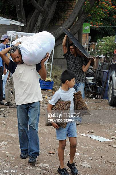 Local residents evacuate on October 24 2008 their homes at El Eden neighborhood on the side of El Picacho hill in Tegucigalpa Some 1000 inhabitants...