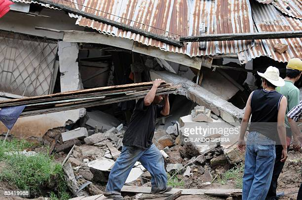 Local residents evacuate their ruined homes on October 24 2008 at El Eden neighborhood on the side of El Picacho hill in Tegucigalpa Some 1000...