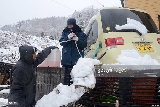 Local residents extract gasoline from a car damaged in the March 11 tsunami to refuel for their vehicle in Miyako in Iwate prefecture on March 16...