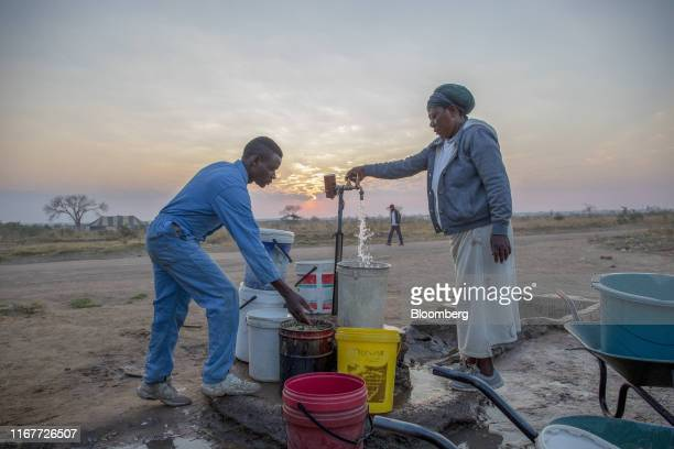 Local residents fill buckets and containers with water at a communal tap as the sun sets in Empompini in Cowdray Park, Bulawayo, Zimbabwe, on...