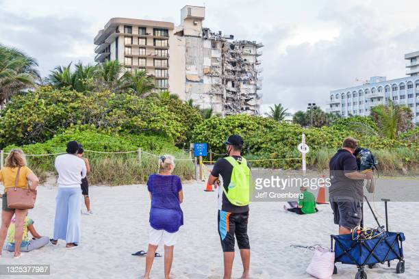 Local residents gather on the beach to look at the collapsed Champlain Towers condimium, Surfside, Miami Beach, Florida.
