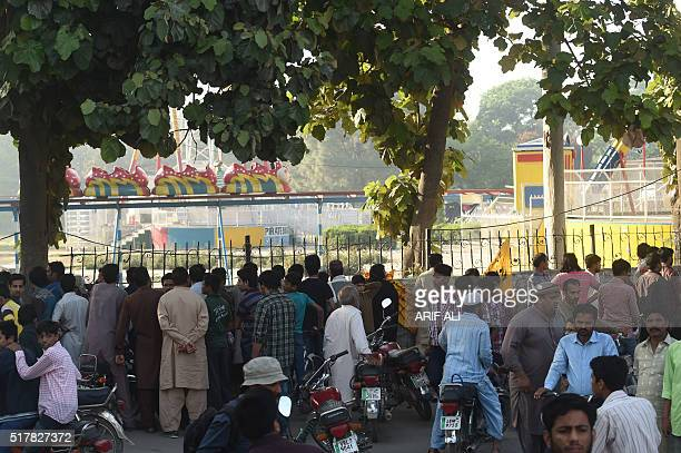 Local residents gather outside the cordonedoff site of the March 27 suicide bombing in Lahore on March 28 2016 The toll from a suicide blast in...