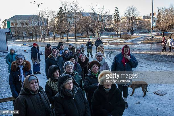 Local residents gather to receive humanitarian aid outside a damaged supermarket on the central square on February 20 2015 in Debaltseve Ukraine...