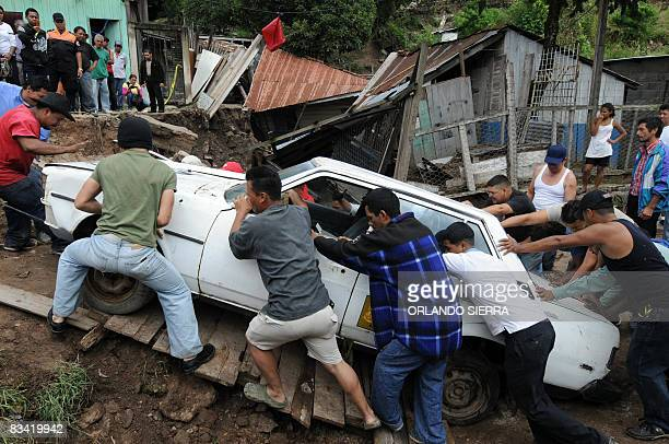 Local residents give a hand to salvage a car from a wrecked sector on October 24 2008 at El Eden neighborhood on the side of El Picacho hill in...
