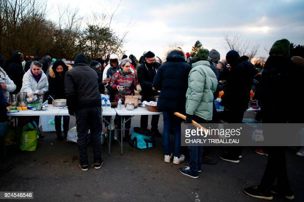 Local residents give food to migrants on February 26 2018 near the port of Ouistreham northwestern France More than a year after the dismantling of...