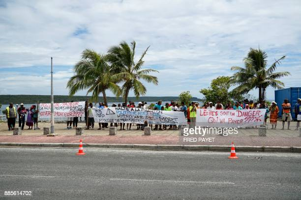 Local residents hold banners reading 'the islands are in danger who's going to pay' and 'stop the polution politicians help us hydrocarbons = death '...