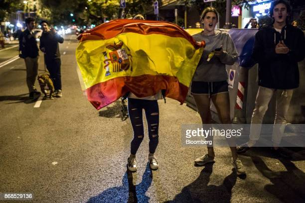 Local residents hold up a Spanish national flag to protest against a demonstration by neoNazi protesters in a residential neighbourhood of the Sant...