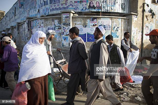Local residents in downtown Kabul Afghanistan walk through a market during the month of Ramadan August 29 2009 Political campaign posters remain from...