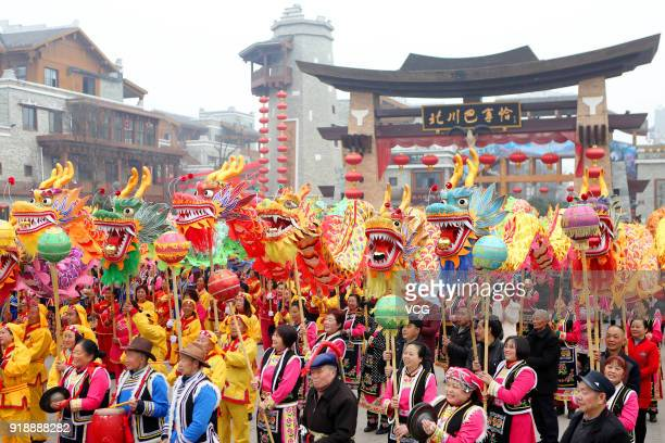 Local residents in festive costumes perform dragon dances together to welcome Lunar New Year on February 16 2018 in Mianyang Sichuan Province of...