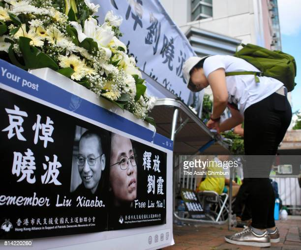 Local residents in Hong Kong place flowers at a makeshift memorial set up for Nobel Peace Prize laureate Liu Xiaobo in front of an office affiliated...