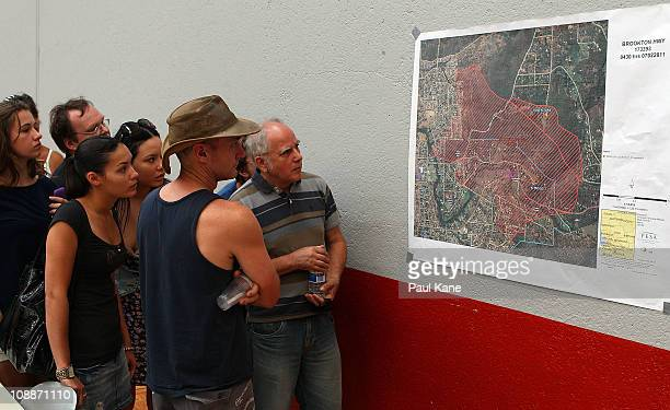 Local residents inspect a map outling the fire damage are during a FESA community briefing on February 7 2011 in Perth Australia Fire and Emergency...