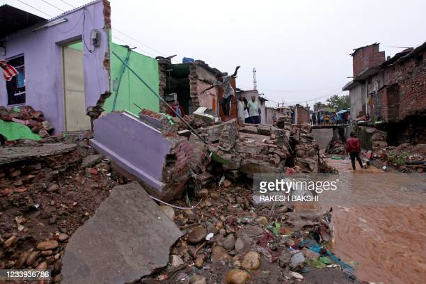 Local residents inspect the debris of their houses that were damaged by flash floods after heavy monsoon rains on the outskirts of Jammu on July 12,...