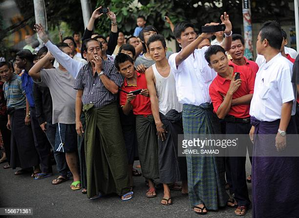 Local residents line up along the street as US President Barack Obama's motorcade drives to the Parliament House in Yangon on November 19 2012 Obama...