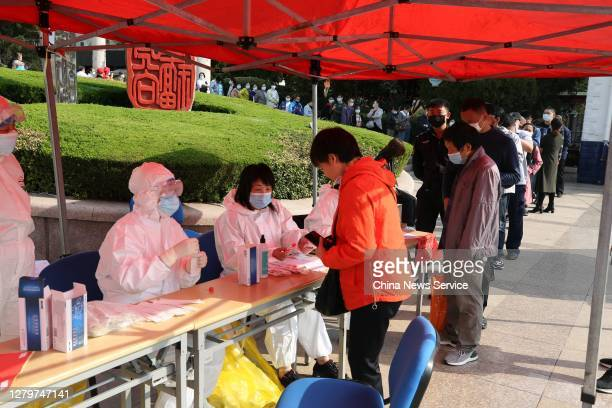 Local residents line up for nucleic acid testing for the COVID-19 coronavirus at a community testing site on October 12, 2020 in Qingdao, Shandong...