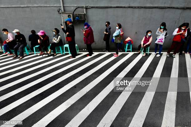TOPSHOT Local residents line up to buy face masks amid concerns of the COVID19 coronavirus from a pharmacy in New Taipei City on March 17 2020
