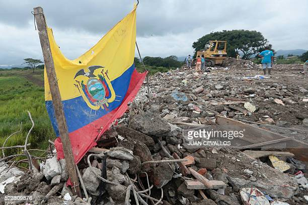 Local residents look around at a rubble dump for things to salvage in Pedernales Ecuador on April 24 2016 Nearly 650 people are now known to have...