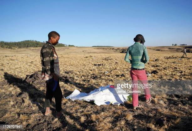 Local residents look at debris at the scene where Ethiopian Airlines Flight 302 crashed in a wheat field just outside the town of Bishoftu 62...
