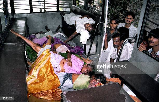Local residents look at the corpses of people killed in a stampede in Lucknow 12 April 2004 At least 21 people were killed in the stampede after...