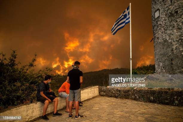 Local residents look at the wildfire approaching the village of Gouves on Evia island, second largest Greek island, on August 8, 2021. - Hundreds of...