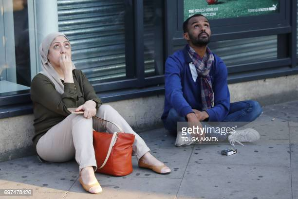 Local residents look up at a helicopter at the scene in Finsbury Park area of north London after a vehichle hit pedestrians on June 19 2017 One man...