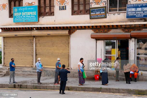 Local residents maintain social distancing as they stand in a queue to buy groceries outside a store during a nationwide lockdown imposed as a...