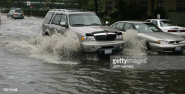 Local residents of Geneva, Illinois, try to drive through a flooded street 24 August, 2007 along the Fox River in Illinois. Flooding along rivers in...